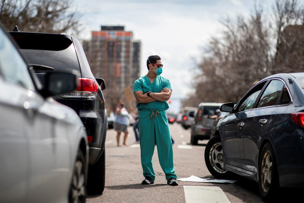 Health care workers stand in the street as a counter-protest to those demanding the stay-at-home order be lifted in Denver.